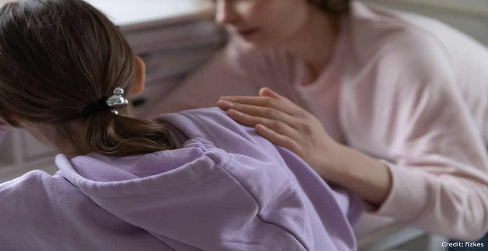 Close up back view of woman comforting upset teenage girl